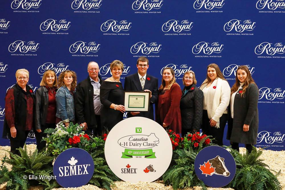 Scholarship recipient standing infront of blue backdrop and other volunteers at the Royal Agricultural Winter Fair