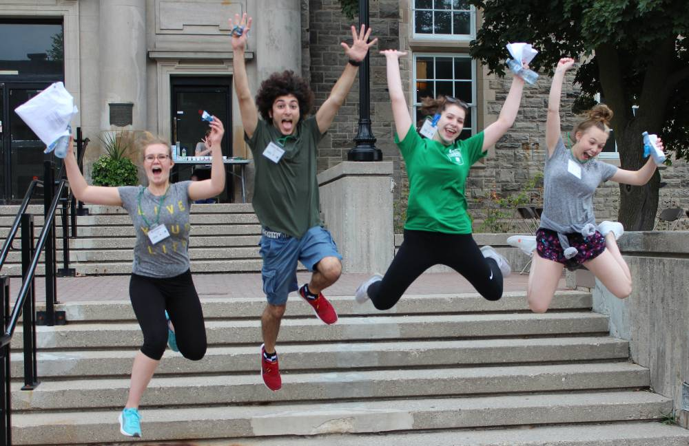 Four youth jumping with hands up in the air.