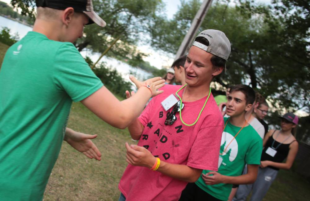 Youth in grass field playing rock, paper, scissors game at camp