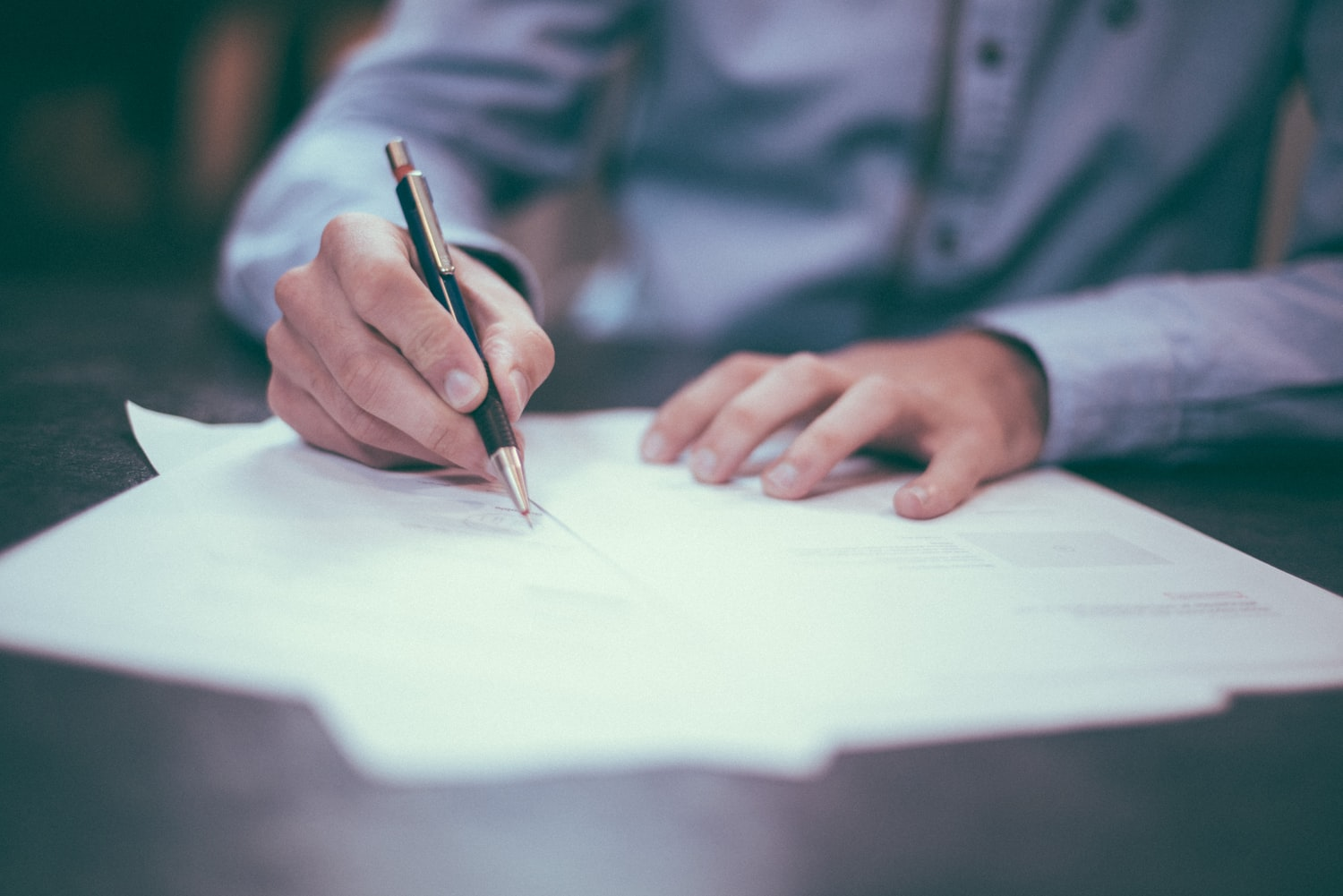 Person filling out form at desk with pen