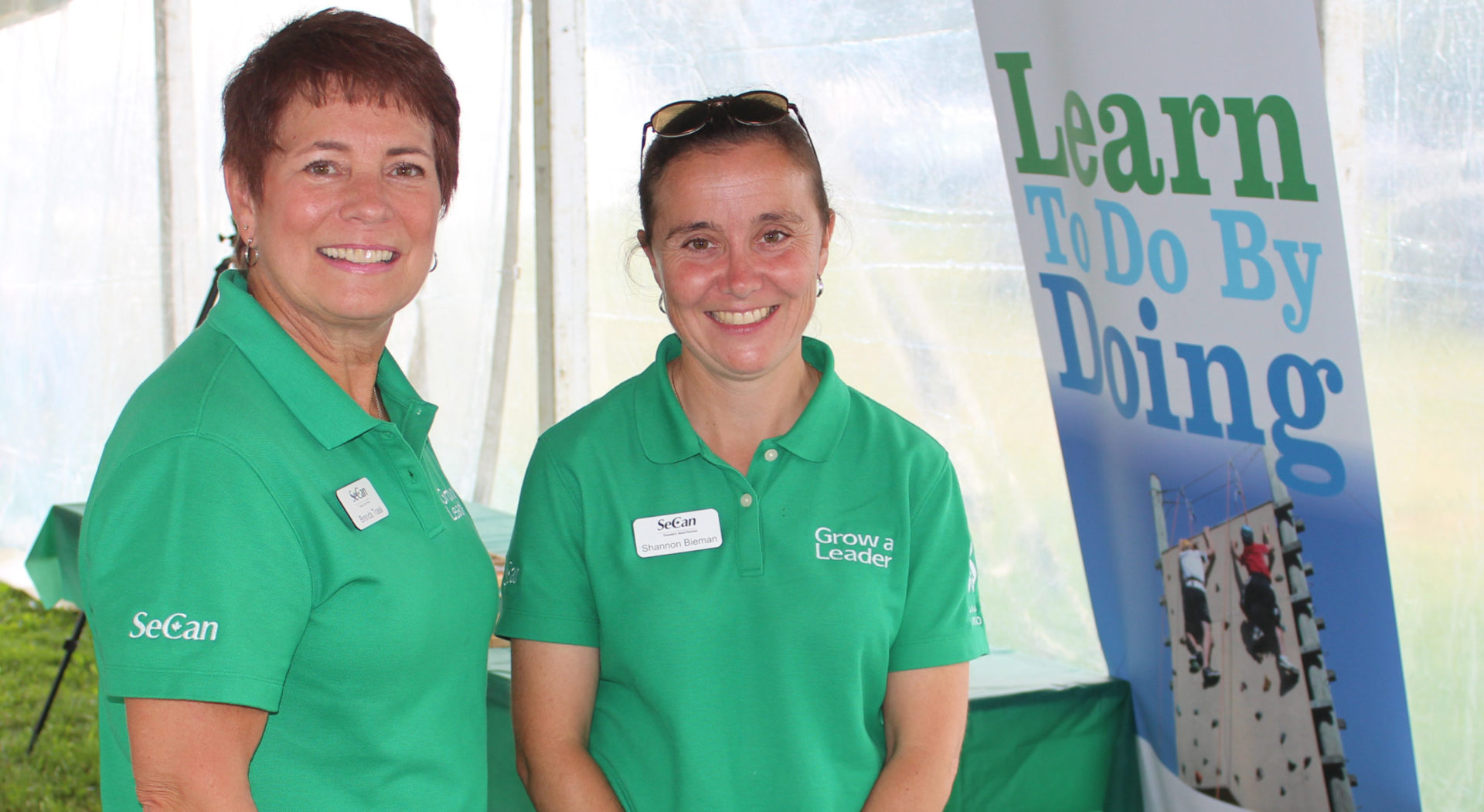 Two people in green polo shirts standing in front of Learn To Do By Doing banner under covered tent.