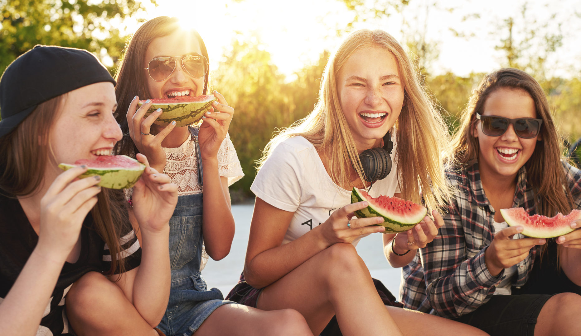 Group of teens sitting in grass eating watermelon