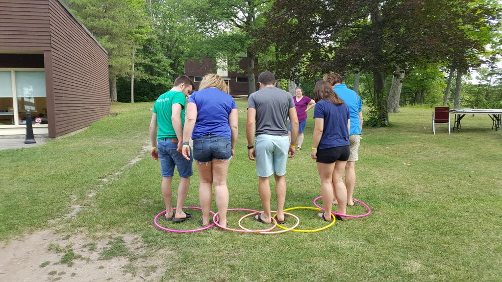 Group of people facing away standing side by side in hoola hoops