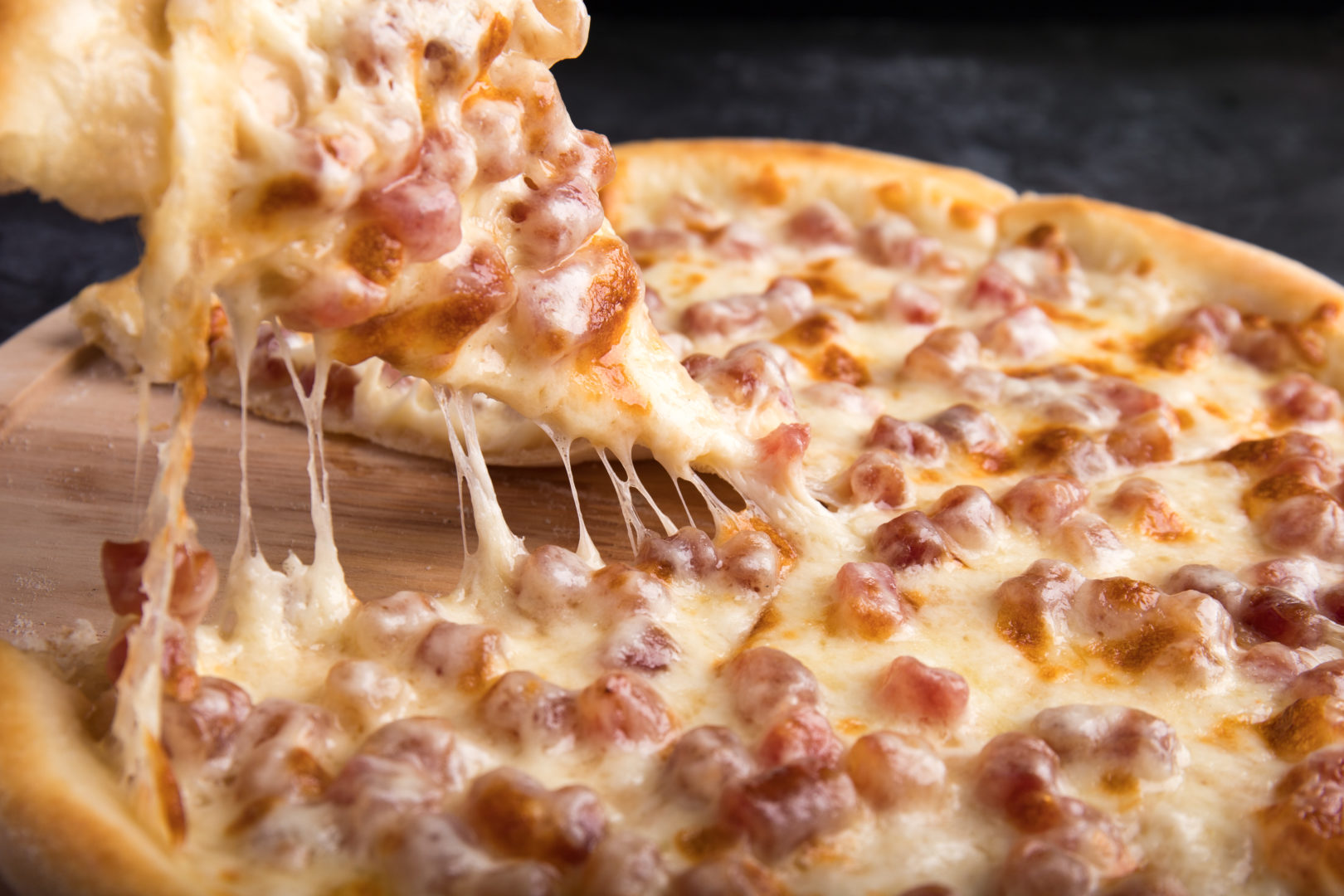 Close up of someone pulling slice from whole pizza