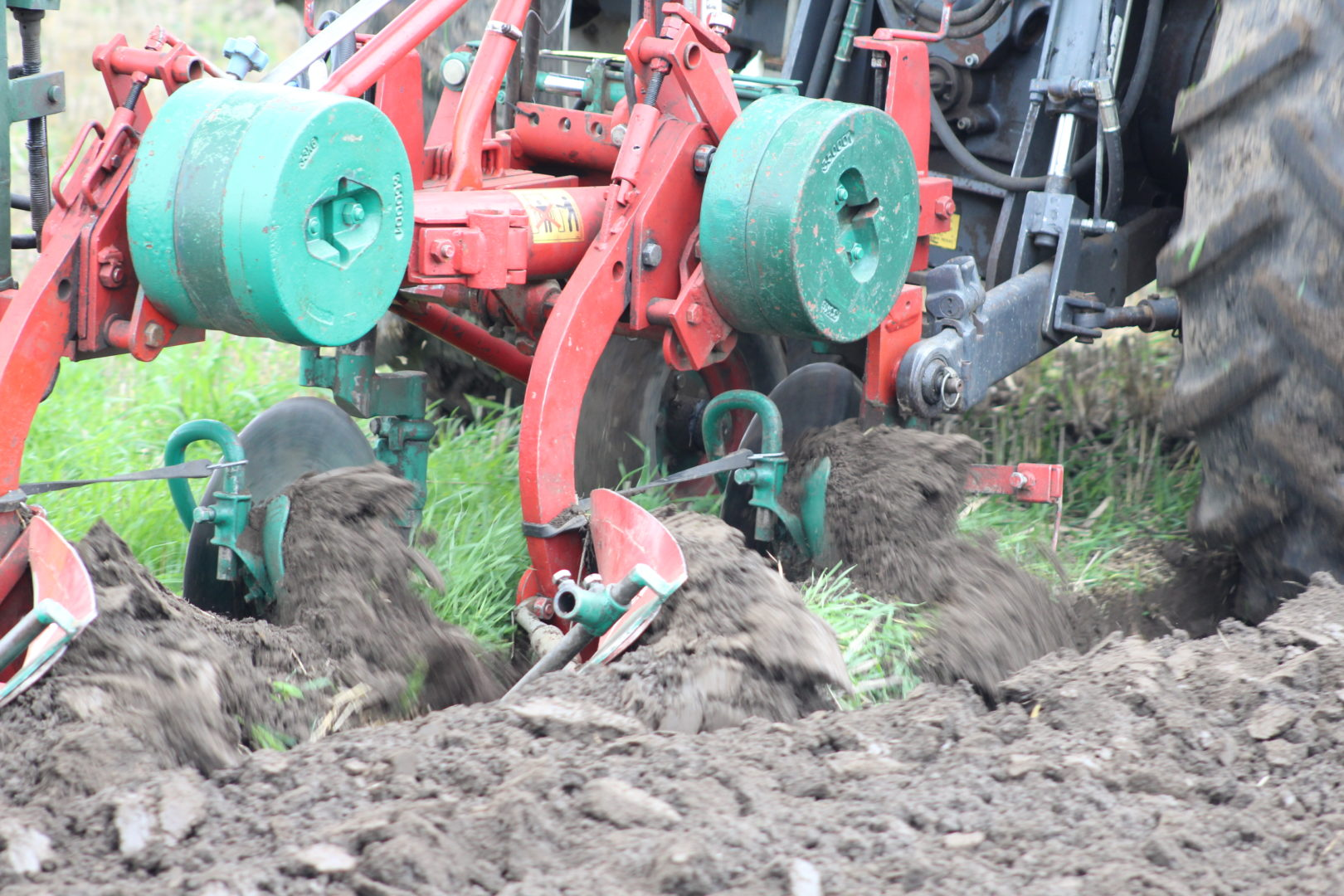 Red and green tractor tilling field