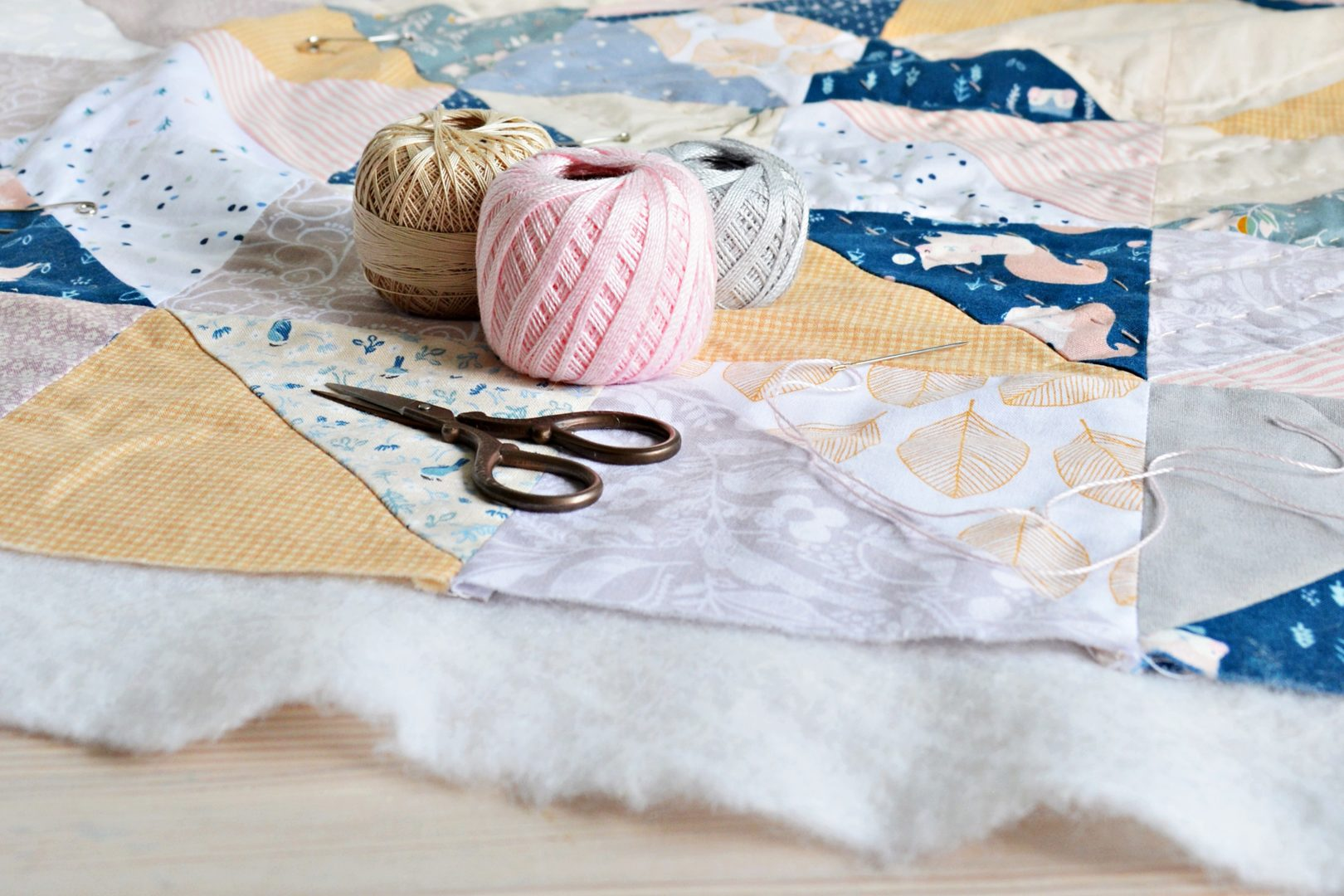 Hand stitched quilt on table with cotton thread, needle and scissors