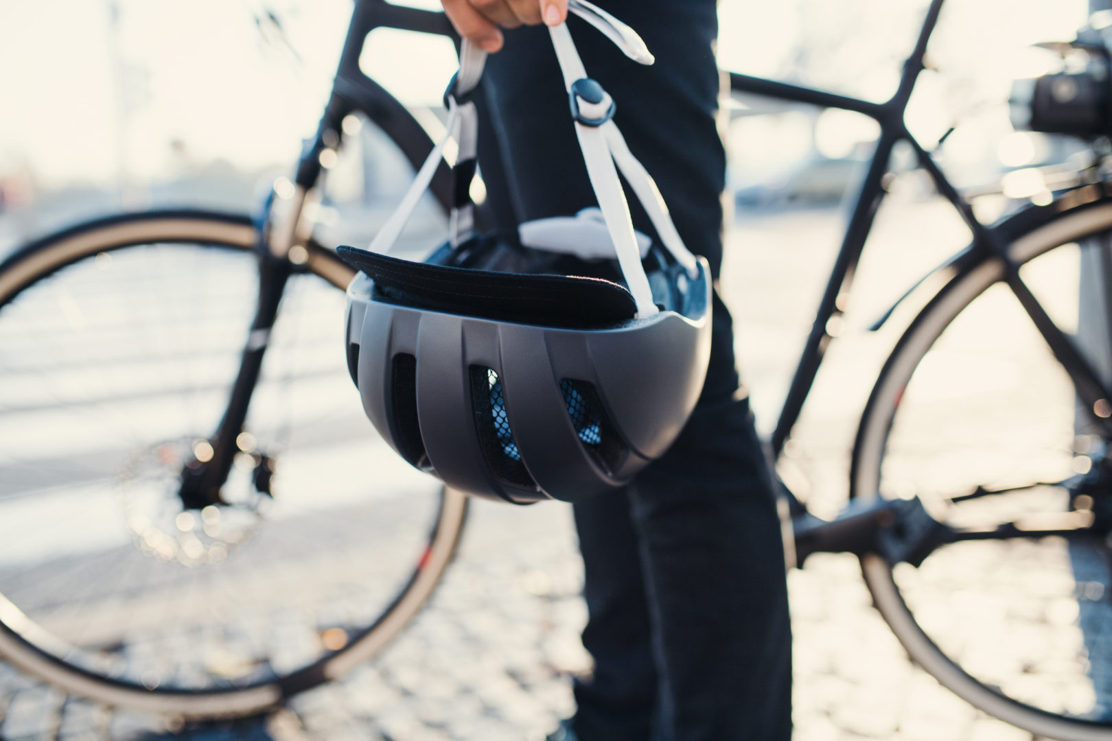 Person holding bicycle helmet in front of bike