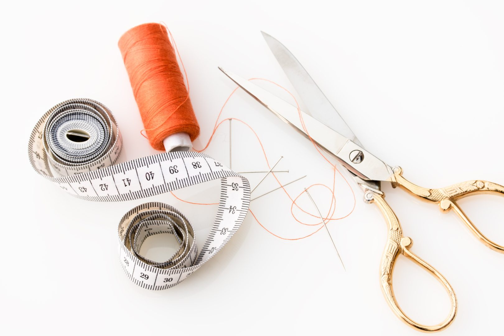 Scissors, pins, orange thread and tape measurer sitting on white table