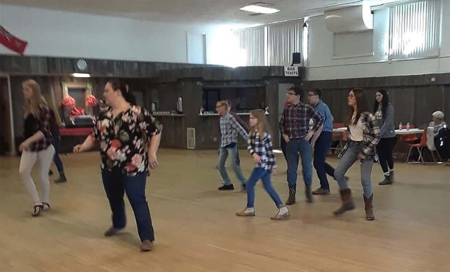 Group of kids and adults learning to square dance in community hall