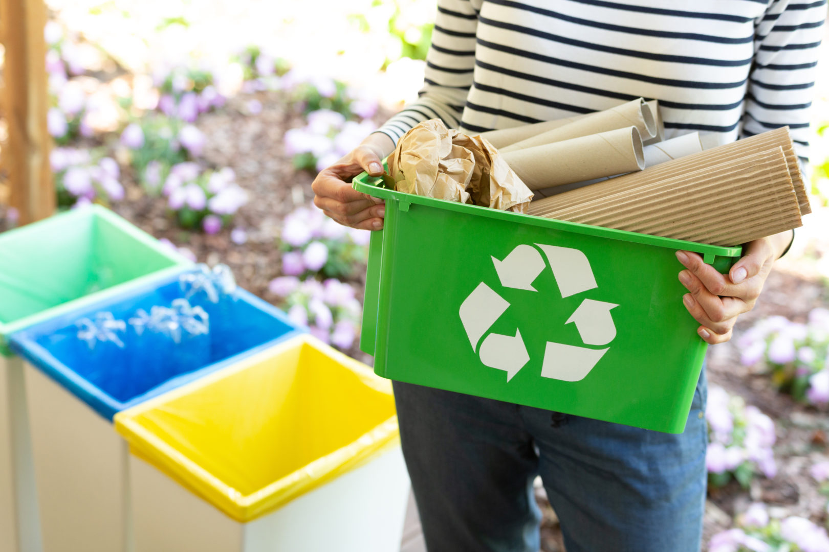 Close up of person holding green basket with recyclign symbol that has papers in it