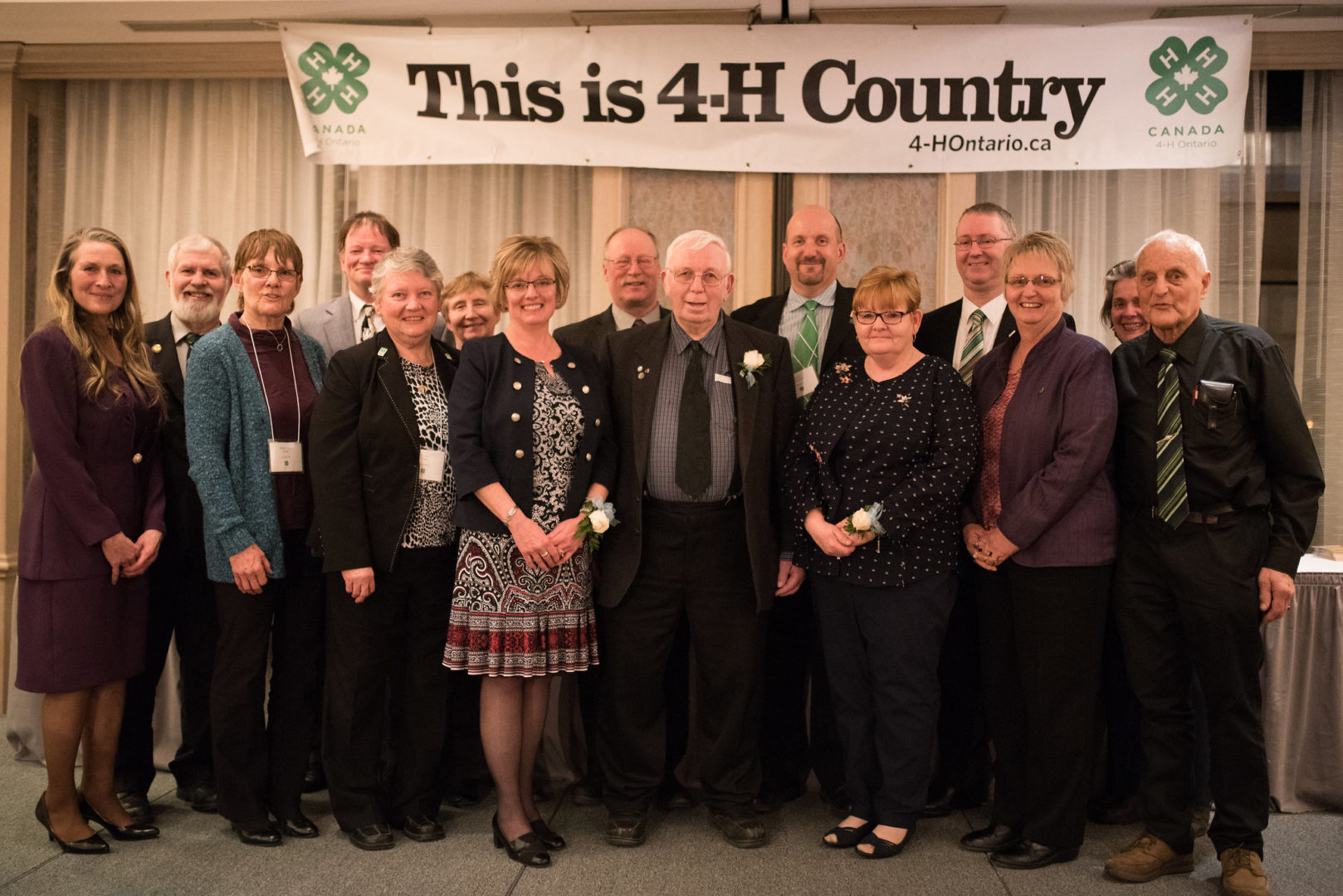 Group of award winners standing on stage in front of 4-H sign