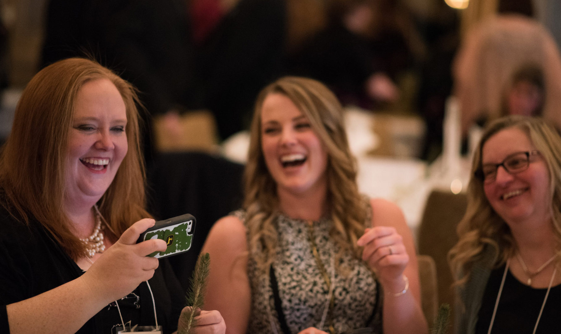 Three people sitting at banquet smiling and laughing looking at phone