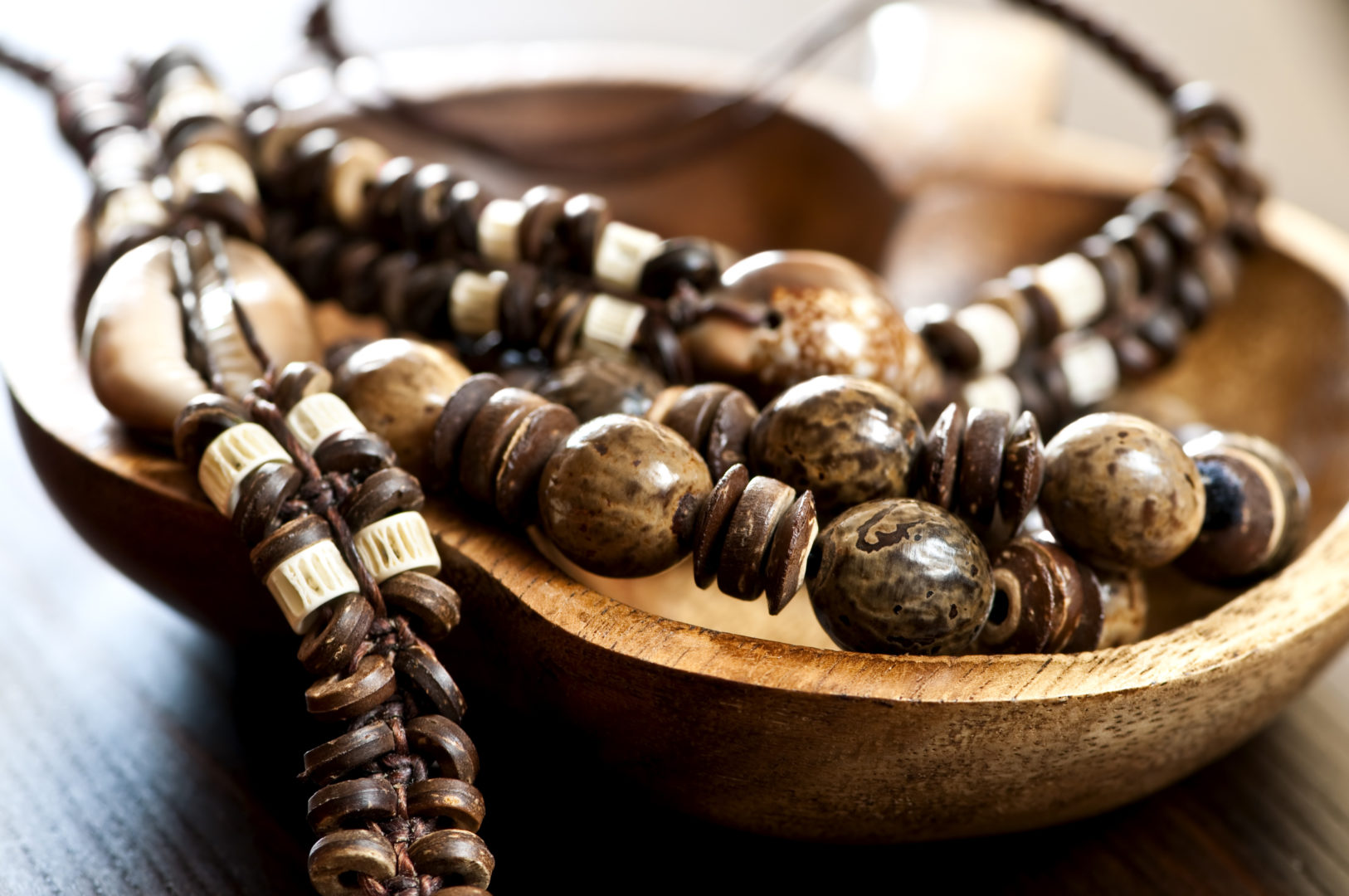 Close up of wooden jewlery in a wooden bowl