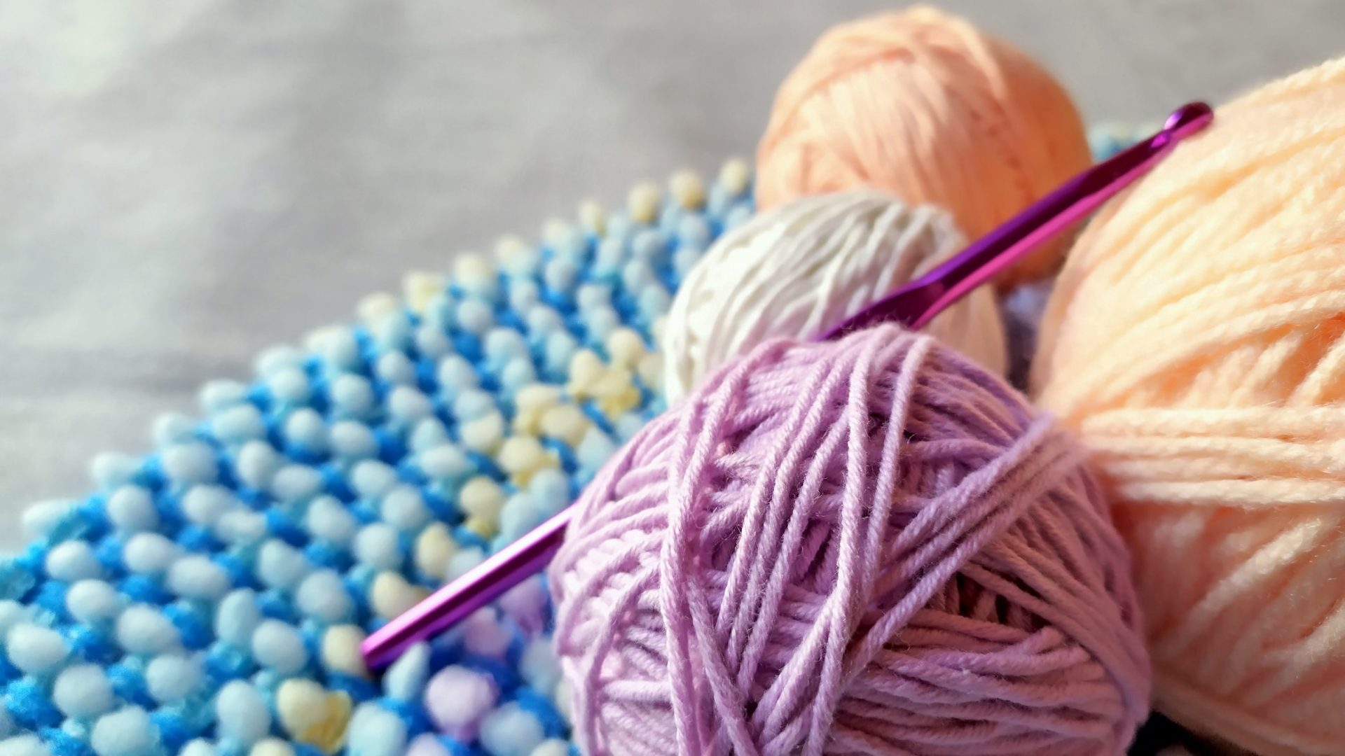 Close up bundles of wool with pink knitting needle