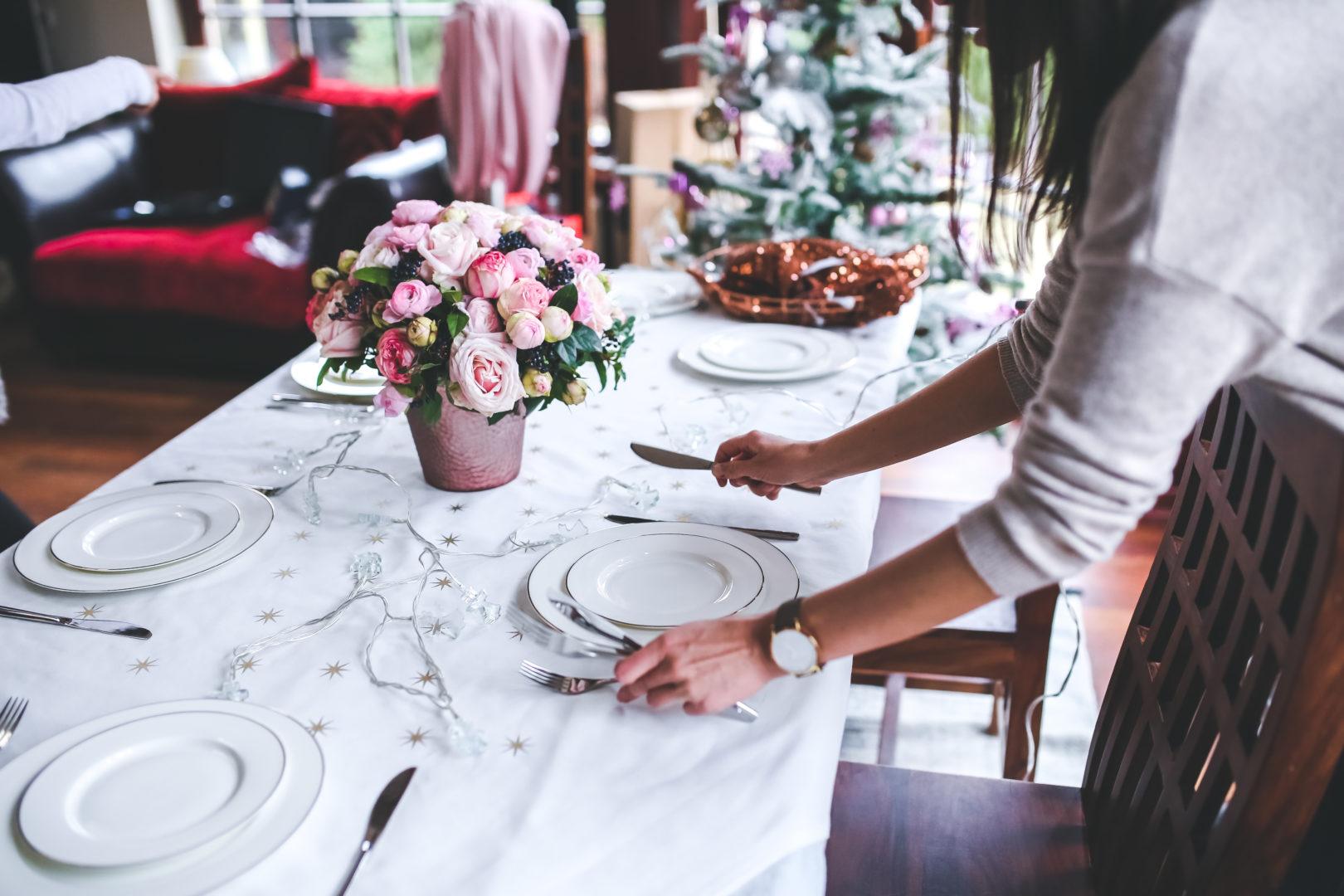 woman setting table at christmas time
