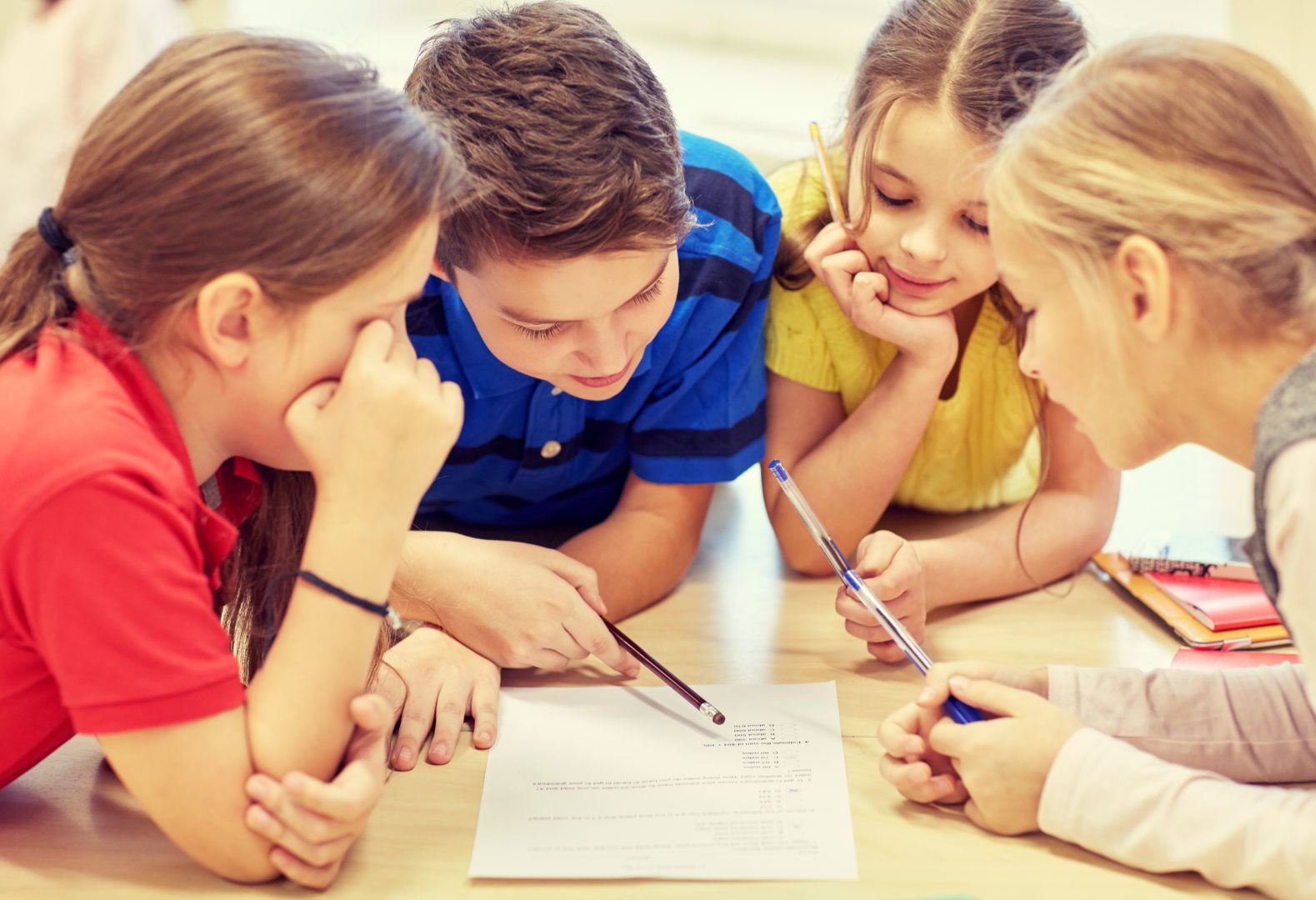 Group of kids filling out activity on paper at table