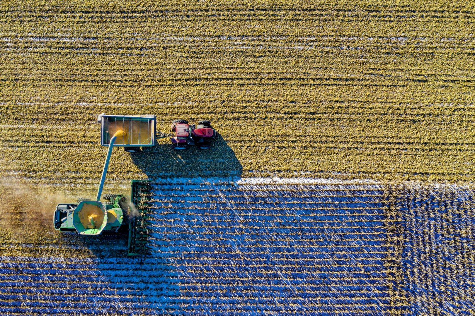 birds eye view of combine and tractor in field