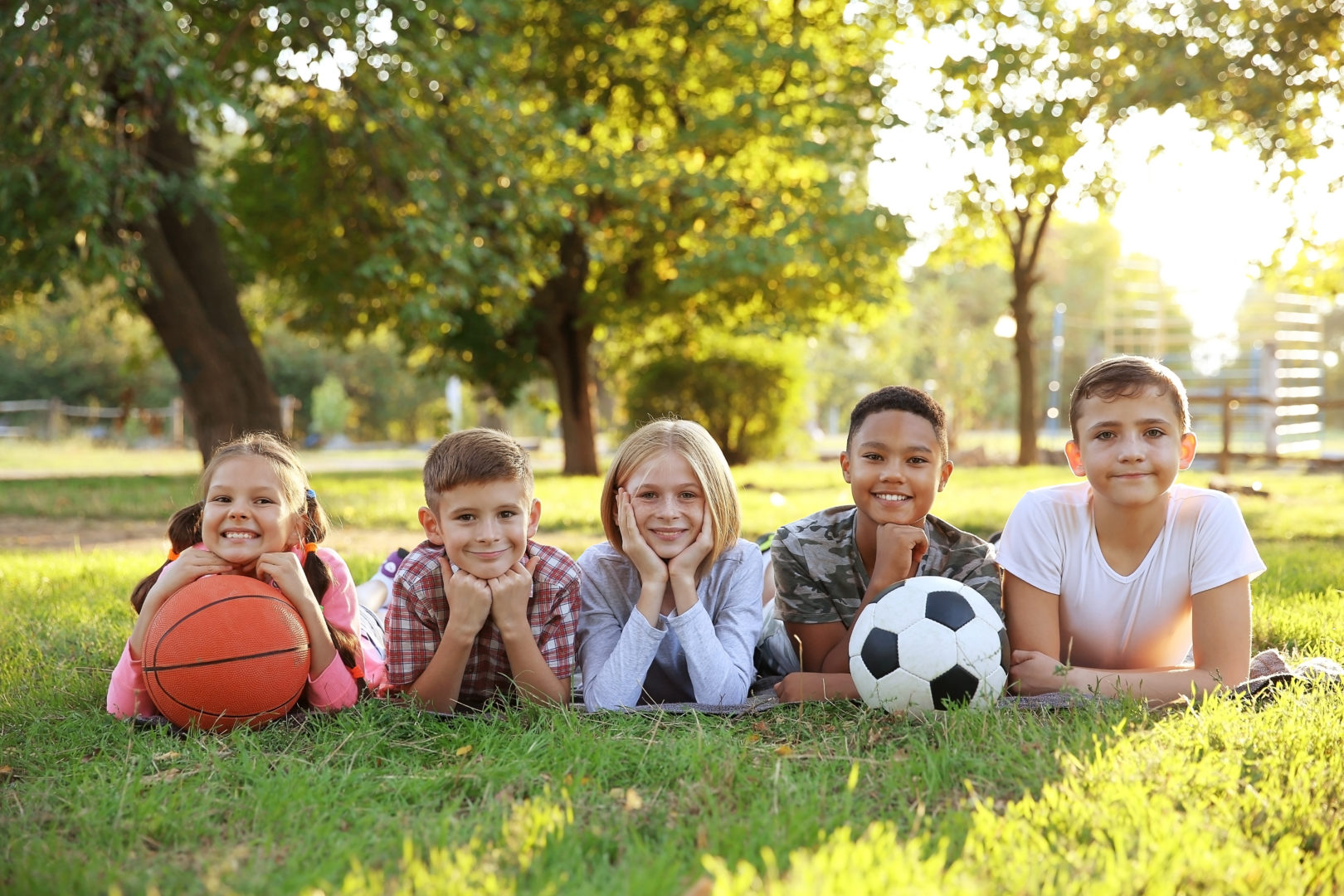 Five kids lying on bellies in grass with soccer ball and basketball