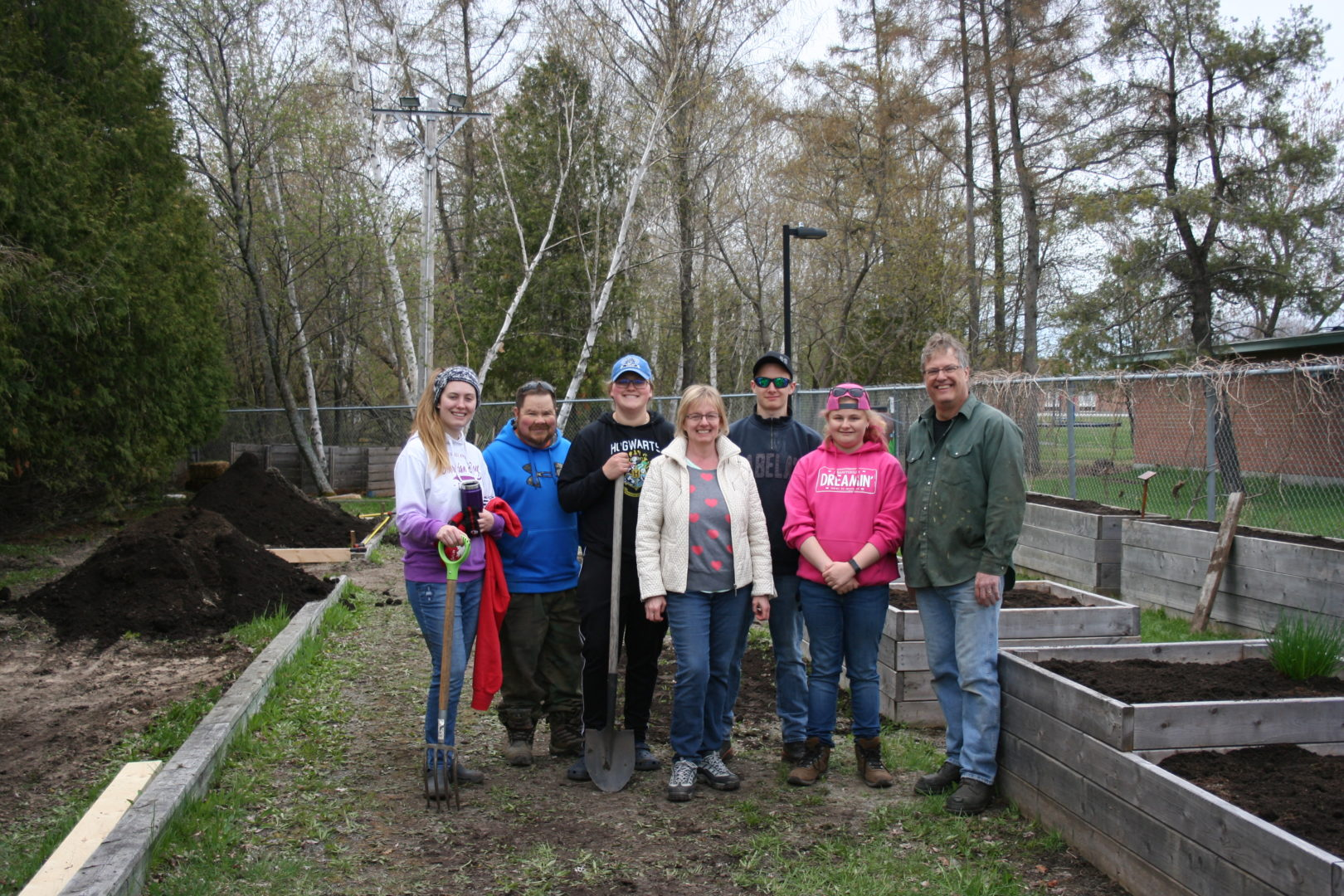 Group of people standing in front of garden boxes with fresh soil