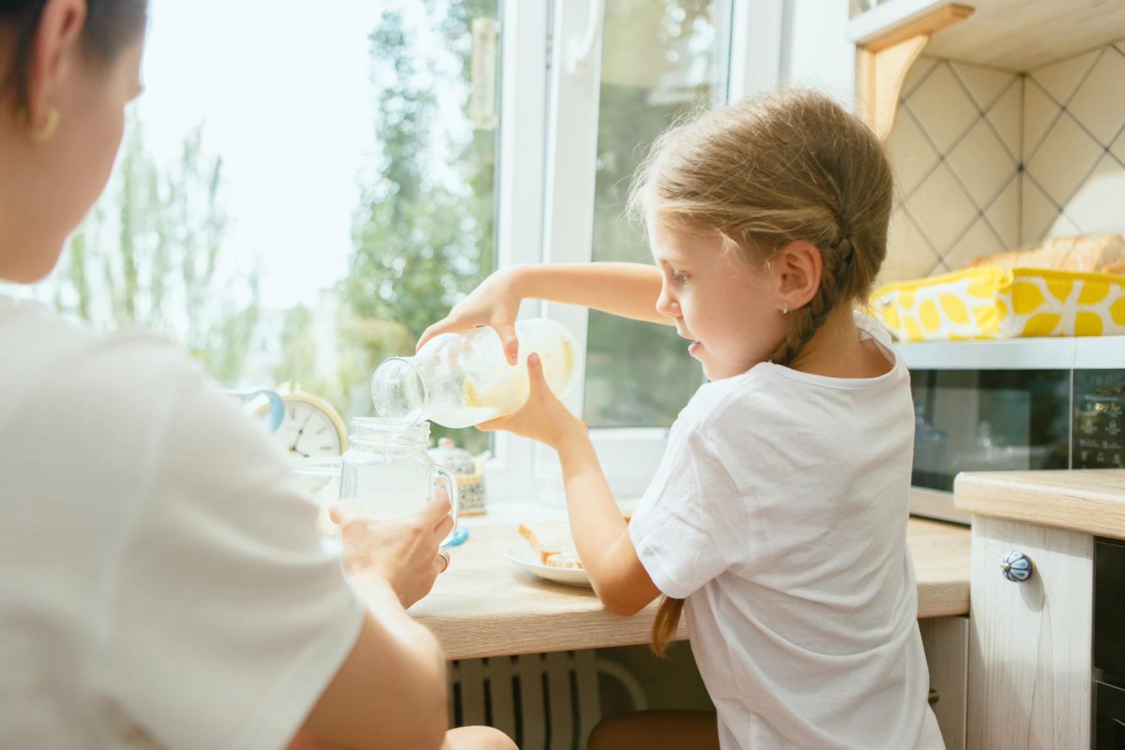Kid standing in kitchen pouring milk into jar