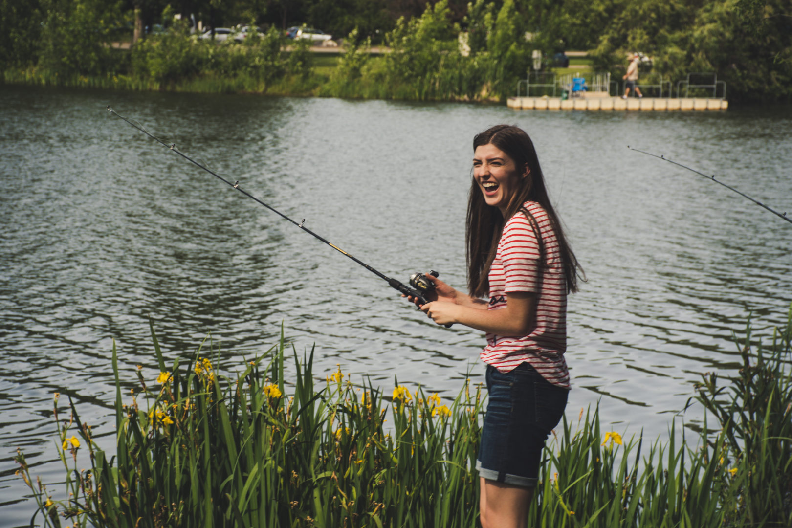 Girl standing in front of lake wish fishing rod in the water