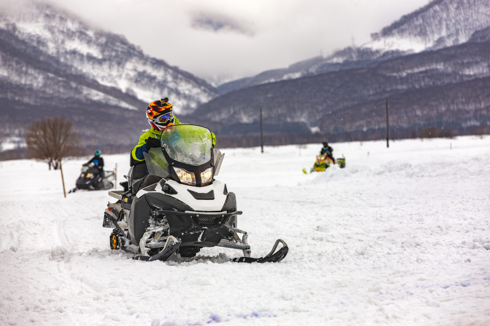 Three people riding snowmobiles in valley surrounded by mountain