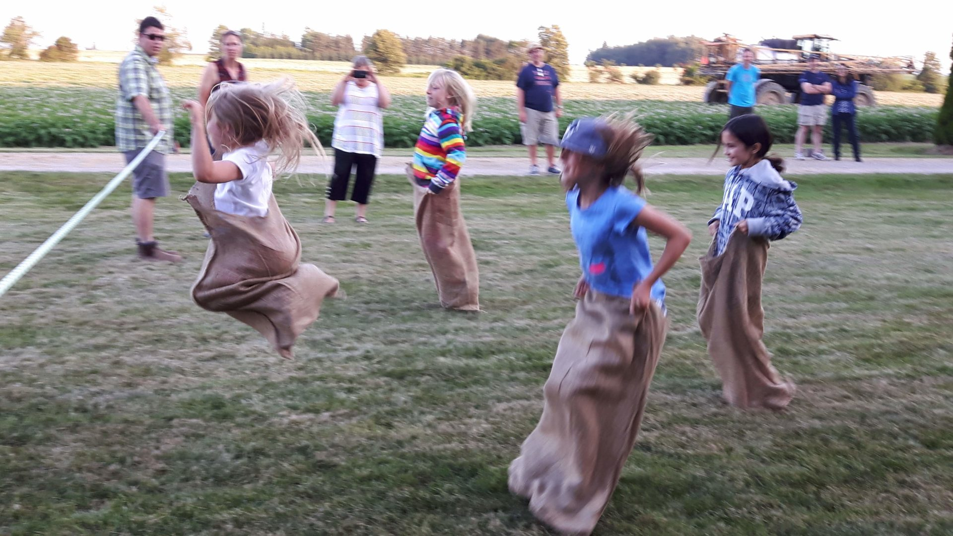 Cloverbud members jumping high to get to the finish line in a potato bag race